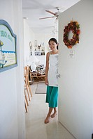 A young woman standing by door