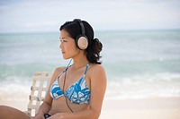 A woman listening to music at beach (thumbnail)