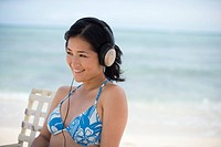 A woman listening to music at beach