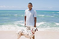 Man standing with dog at beach