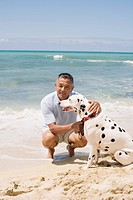 Man crouching with dog at beach