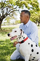 Profile of man sitting with dog in park