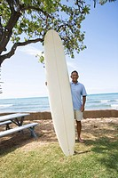 Man standing with surfboard (thumbnail)