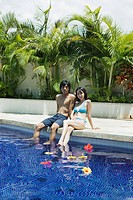 A young couple sitting near pool