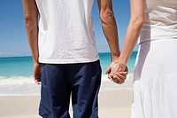 Midsection of a couple holding hands at beach