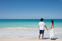 A young couple holding hands at beach