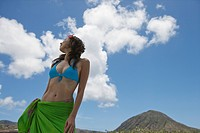 Low angle view of a young woman standing under cloudy sky