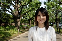 Portrait of a young woman smiling with trees in background