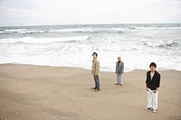 Son with father and grandfather standing at beach