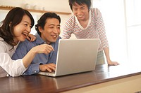 Young man with mother and father, using laptop