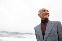 Senior man at beach, smiling (thumbnail)