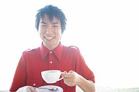 Young man holding tea cup, portrait