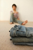 Young man sitting by wall while jeans on foreground (thumbnail)