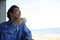Mature man drinking tea, side view