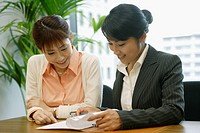 Two woman express happiness as they look over the sheet of the file