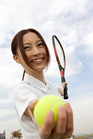 Young woman holding a tennis ball and a racquet
