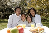 Portrait of a family smiling in garden by breakfast table
