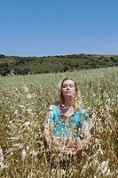 Woman sitting on a field of Naxos, Cyclades Islands, Greece