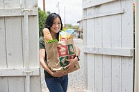 Portrait of a woman holding groceries with paper bag