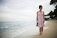 A woman walking on beach with sandal in hand