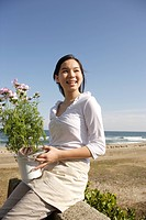 Teenage girl 14_15 holding flower pot at beach, side view