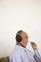 Senior man listening music, side view