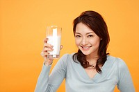 Young woman holding glass of milk, smiling, portrait