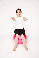 Senior woman sitting on exercising ball with arms raised