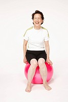 Senior woman sitting on exercising ball, smiling