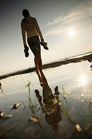 Barefoot female jogger standing at lake Starnberg, Ambach, Bavaria, Germany