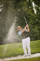 Man hitting a golf ball out of a sand trap, Strasslach_Dingharting, Bavaria, Germany