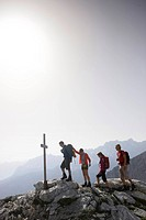 Hikers near summit cross, Wetterstein range, Bavaria, Germany