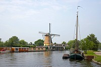 A windmill and a sailing boat at the riverbank of the river Vecht at Vreeland, Netherlands, Europe
