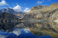 Reflection of mountains on lake Bacino del Truzzo, Oberhalbstein Alps, Chiavenna, Sondrio, Lombardy, Italy