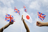 Three people holding British and Japanese flag against sky, low angle view
