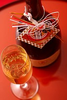 Champagne flute and bottle against red background, close_up