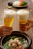 Two people toasting with beer, close_up