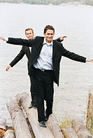 Two smiling businessmen in suits balancing on driftwood