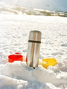A thermos and cups in the snow.
