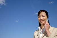 Japan, Honshu, Tokyo, Young businesswoman using mobile phone, smiling