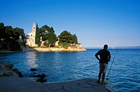 Angler on the beach in front of Dominican abbey under blue sky, Brac island, Croatian Adriatic Sea, Dalmatia, Croatia, Europe