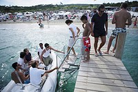 People climbing from a jetty in a dinghy, Ramatuelle, Cote d´Azur, South of France, France, Europe