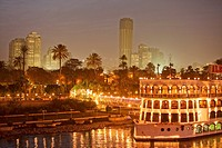 Illuminated ship on the Nile in front of palm trees and high rise buildings, Cairo, Egypt, Africa