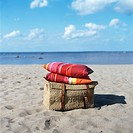 Pillows on a basket on a beach.