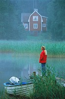 Woman standing on lake pier in evening mist in Sweden