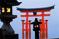 Itsukushima Torii temple gate in the sea in misty twilight on Miyajima Island. Japan