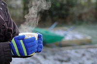 Gardeners hands in gloves, holding steaming cup of coffee in garden, with frosty garden in background, England, january
