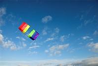 Brightly coloured box kite, flying over deserted beach, blue sky overhead, Norfolk, England