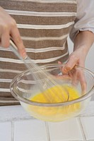 View of hands mixing egg yolk with whisk