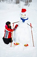 A girl making a snowman.